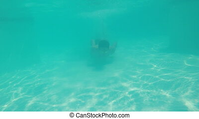 Video shooting underwater with man swimming wearing special...