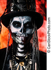 voodoo skeleton man - A man with a skull makeup dressed in a...