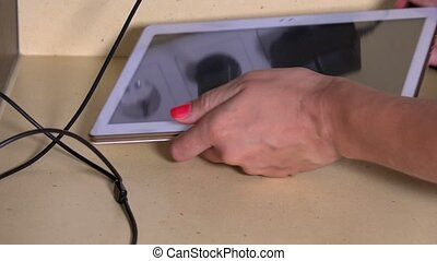 woman hands plug tablet computer and smart phone to wall...