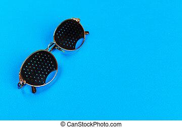 Black pinhole glasses on blue background. Medical concept....