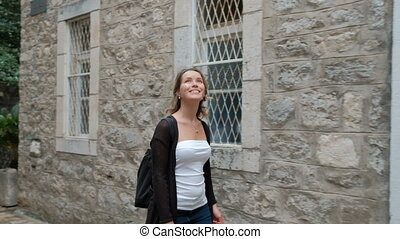 Woman happily walks through ancient stone streets during...