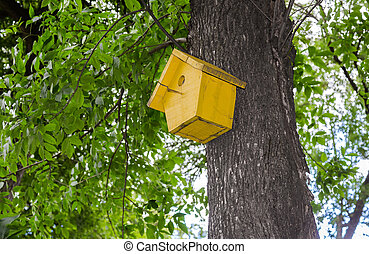 Wooden birdhouse hanging from a tree with green leaves