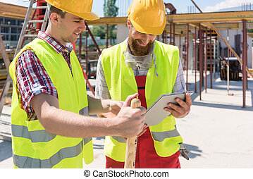 Two young construction workers smiling while using a tablet...