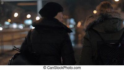 Two women talking when taking walk in evening winter city -...