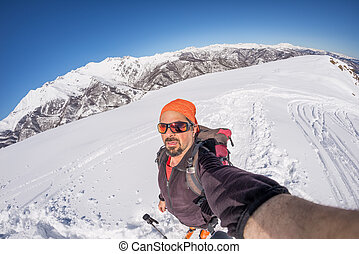 Adult alpin skier with beard, sunglasses and hat, taking...