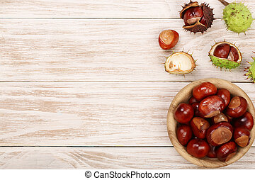 chestnut in bowl on white wooden background with copy space...