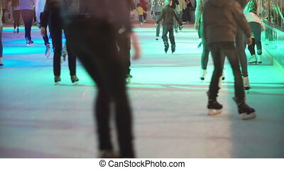 Big crowd of young people skating on the indoor ice rink...