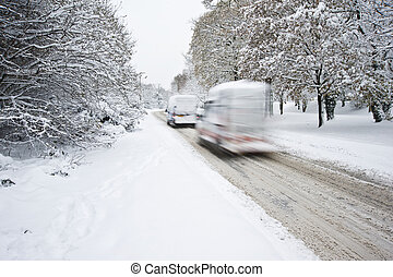 Road in deep Winter snow with blurred moving cars