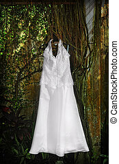 Wedding Gown - White wedding gown against wall of plants