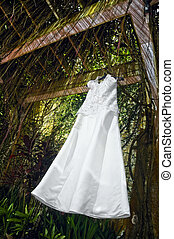 Wedding Gown - White wedding gown hanging on a trellis with...