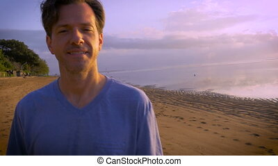 Hand held shot of middle aged man on beach agreeing and talking to the camera