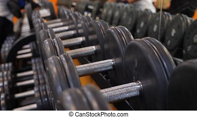 dumbbells lying in a row in the gym. 4k. Slow motion.