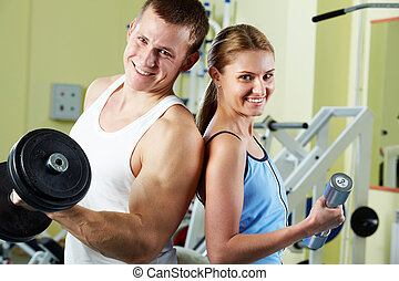 Sporty people - Portrait of sporty couple with dumbbells...