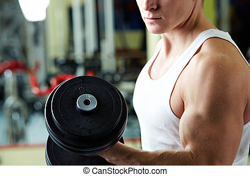 Power - Close-up of sporty man training in gym with barbell