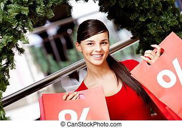 Happy shopper - Happy girl holds red paperbags with symbol...