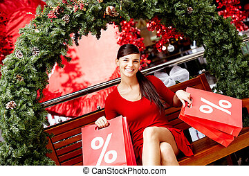 Christmas sale - Happy girl holds red paperbags with symbol...
