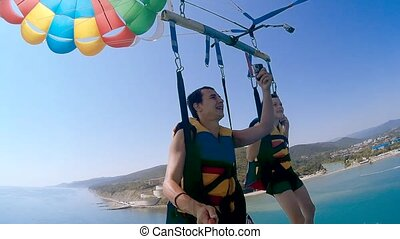 paragliding and ocean parasailing lifestyle. man and boy are...