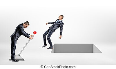 A businessman turns a large lever switch while another man falls back to an open square hole in the ground.