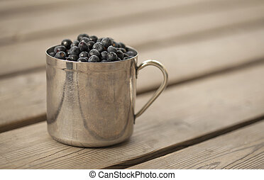 mug filled with bilberry - old scratched stainless steel mug...