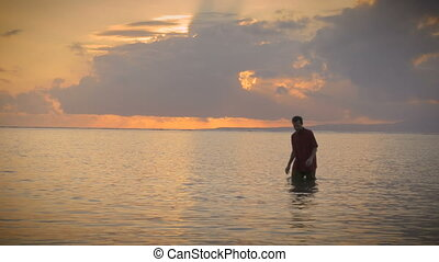 Man walks out of the ocean during a sunset with rays of...