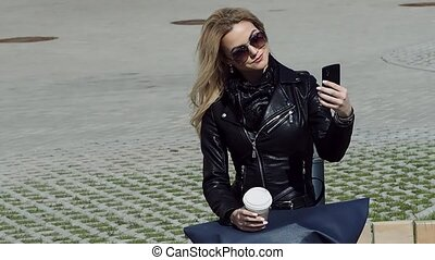 Fashionable girl in leather jacket taking a selfie on...