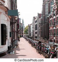 Street with typical Dutch houses and bicycles in Amsterdam.