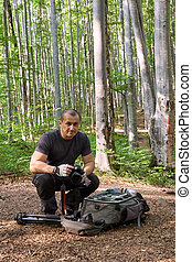 Photographer with camera in the forest