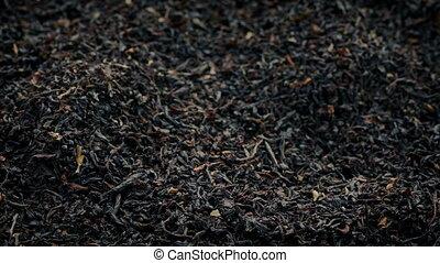 Black Tea Leaves Pouring Into Pile - Black tea leaves pour...