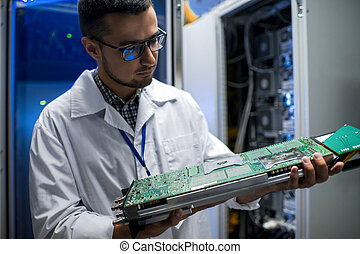 Scientist Inspecting Supercomputer - Portrait of young...