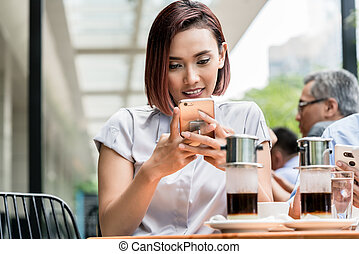 Portrait of a young Asian woman using a mobile phone at a coffee