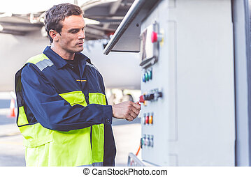 Serious airport staff controlling tool - Side view serene...