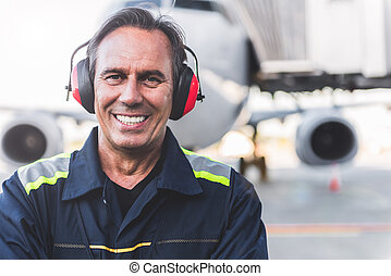 Smiling technical staff situating at airdrome - Portrait of...