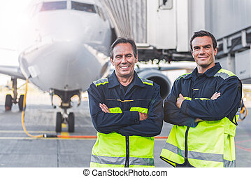 Beaming workers having job at airdrome - Portrait of...