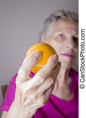 Senior woman doing exercises with a ball in her hands -...