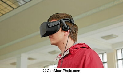 Young man in VR headset playing virtual game - Teenager in...