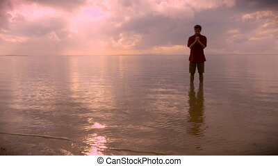 Man stands in calm water of ocean praying during sunrise - A...