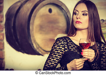 Woman tasting wine in rural cottage interior - Elegant...