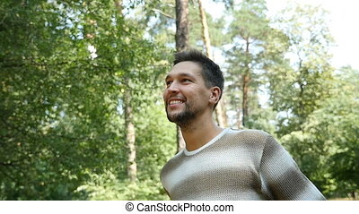 A cheerful bearded man smiles in a pine forest standing in...