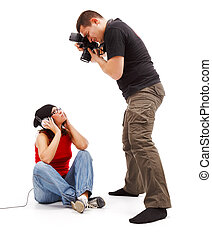 Photographer taking photos of a sitting young model with...