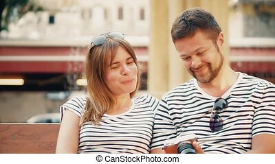 Young happy couple watching photos in the camera on their...