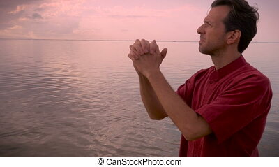 Hand held shot of a man closing his eyes in prayer standing...