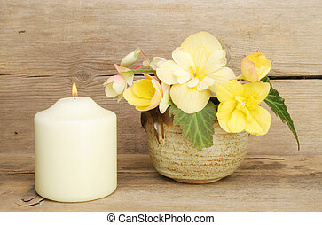 Begonia flowers and candle - Arrangement of yellow begonia...