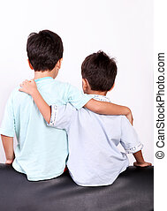 brotherhood - two children hugging back over white...