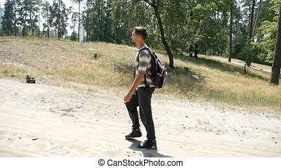 A relaxed man with a rucksack hikes in a pine forest in summer in slow motion