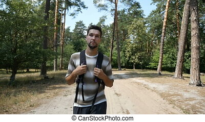 Young man with a backpack walks along some pine forest in summer in slo-mo