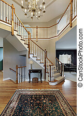 Foyer with wood trim railing on stairway