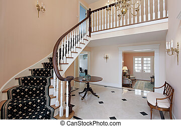Salmon colored foyer with curved staircase and carpeted...