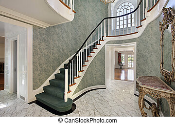 Foyer with green stairs and second floor round window