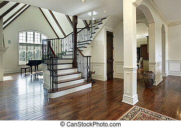 Foyer in luxury home with arched entry into dining room
