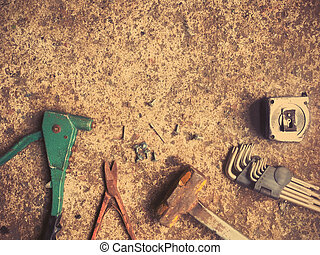 Set of craftsman tools and screws on dirty concrete floor,...